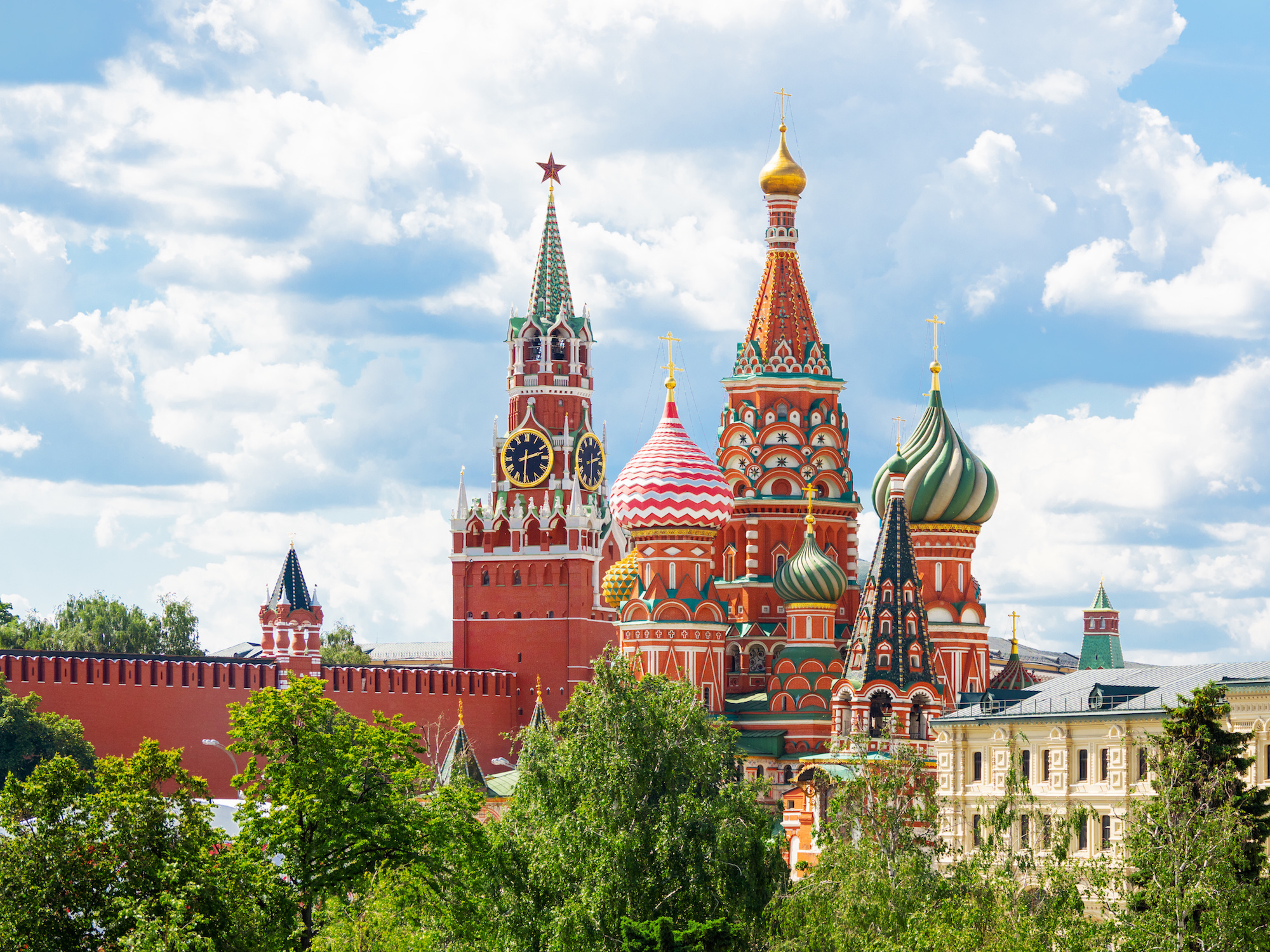 View on Saint Basil Cathedral and Spasskaya tower of Kremlin from Zaryadye park. Famous landmarks in sunny summer day. Moscow, Russia.
