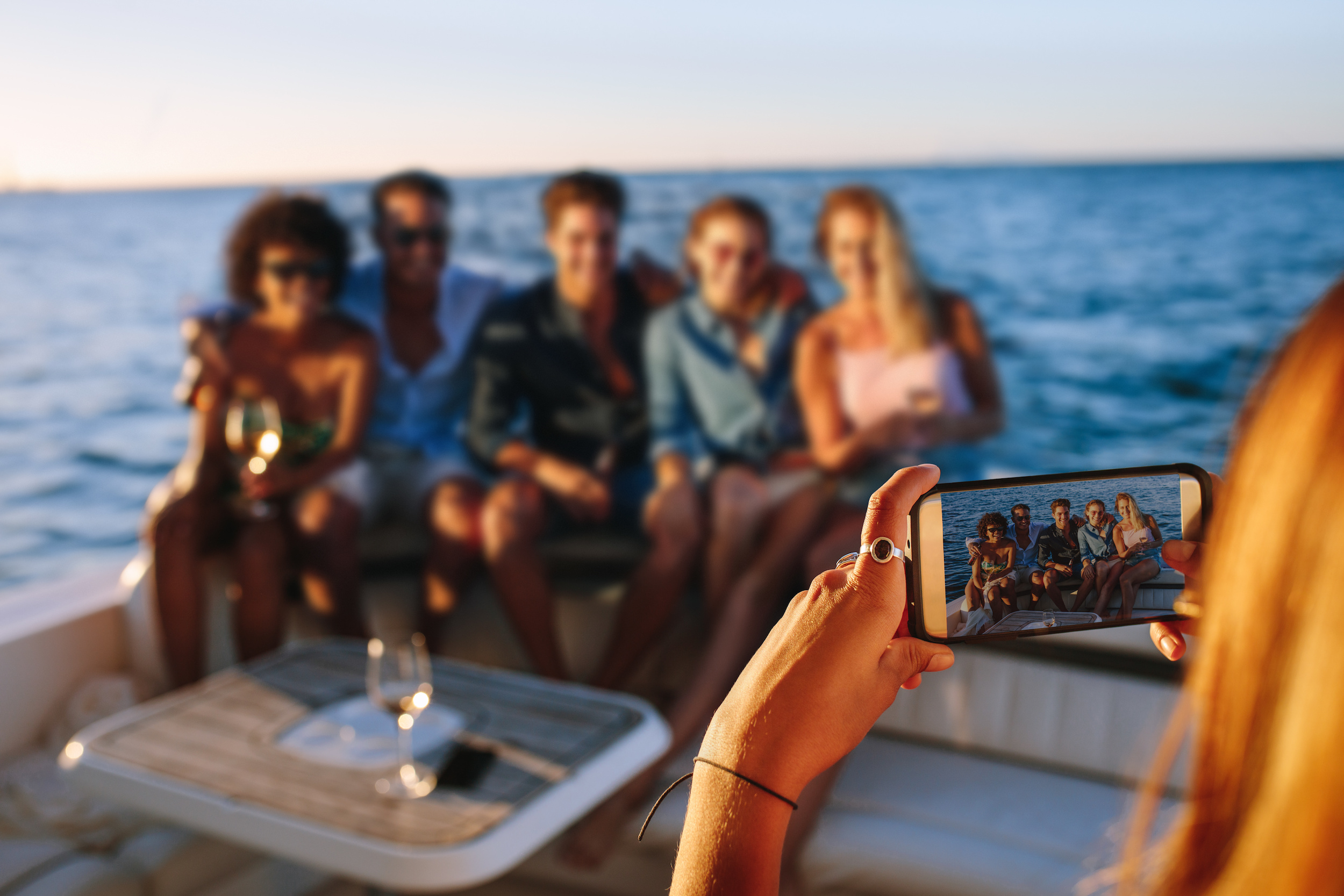 Woman taking a picture with mobile phone of her friends sitting on boat. Capturing memories of boat party.